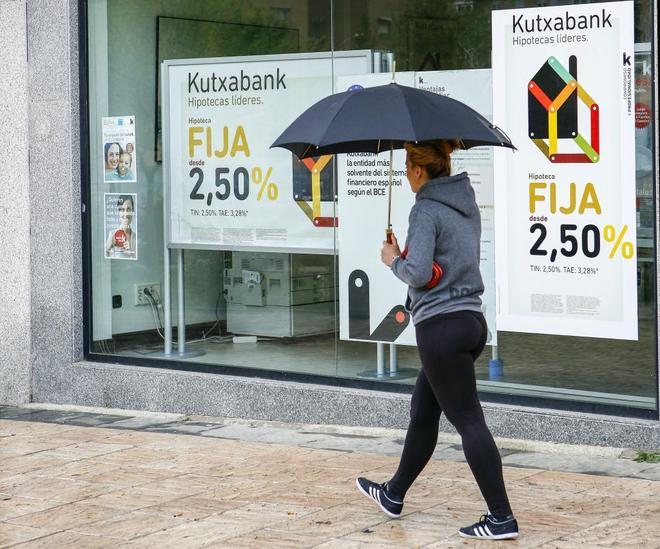 Una ciudadana camina frente a una sucursal bancaria en la que se promocionan hipotecas.