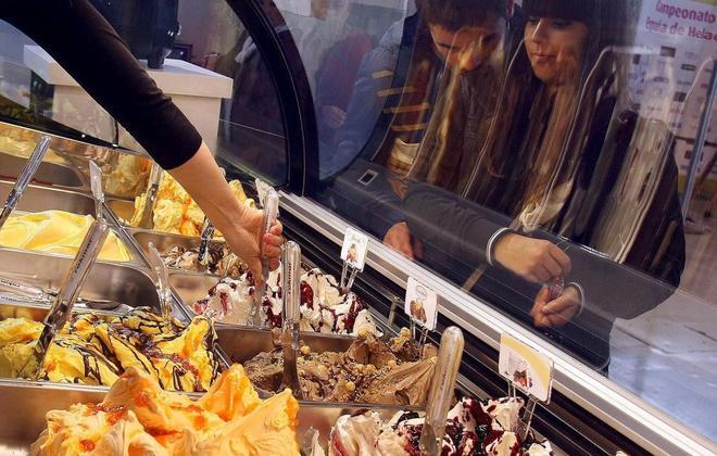 Dos jóvenes esperan a ser atendidas en una heladería.