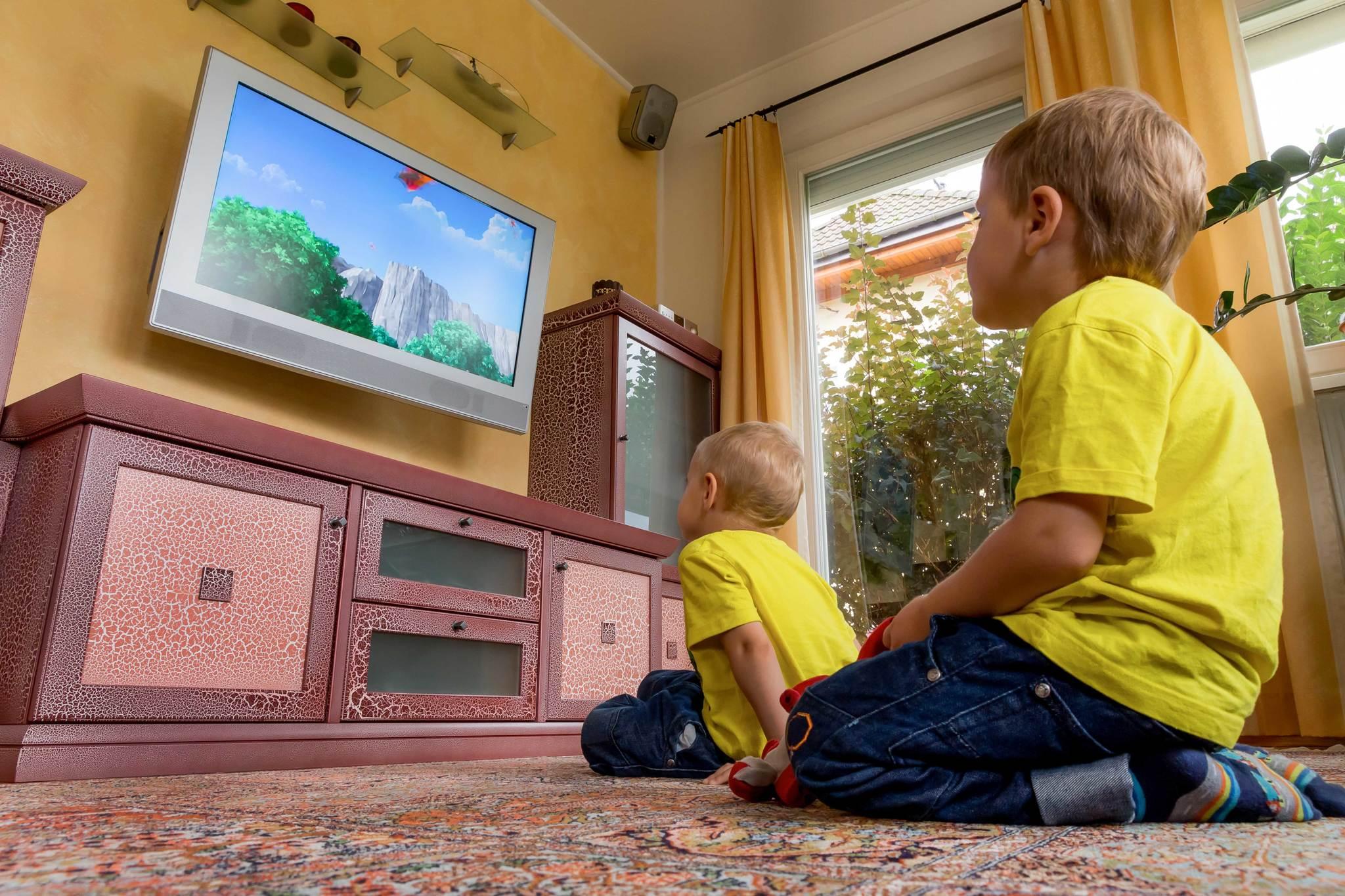 Dos hermanos viendo la tele.
