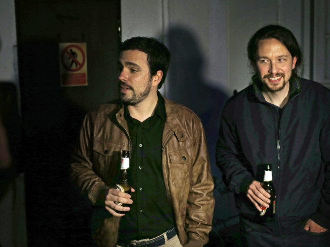 Alberto Garzón y Pablo Iglesias sostienen sendos botellines de...