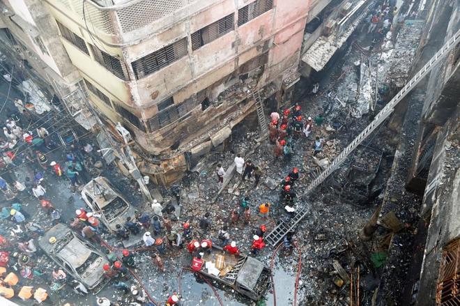Bomberos inspeccionan los escombros tras el incendio declarado en el casco viejo de Dacca.