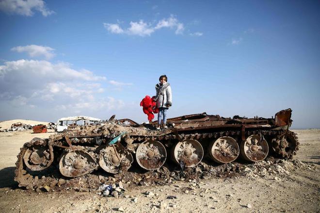 Rawan, una niña siria de 11 años, posa con su oso de peluche sobre un tanque a las afueras del pueblo de Yazi Bagh (Siria), cerca de la frontera con Turquía.