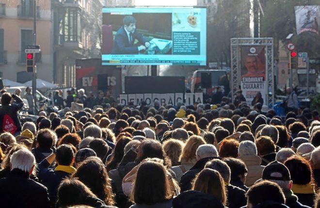Simpatizantes de ANC, siguiendo la declaración de Jordi Sànchez en una pantalla gigante.