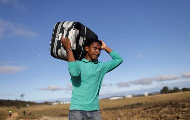 Un hombre carga una maleta en la frontera entre Venezuela y Brasil.