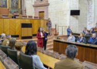 La presidenta del Parlamento andaluz, Marta Bosquet, explica este sábado el funcionamiento del pleno a un grupo de visitantes durante la jornada de puertas abiertas.