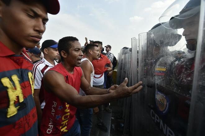 Venezolanos piden a la policía de Venezuela que permitan el acceso de la ayuda humanitaria al país.