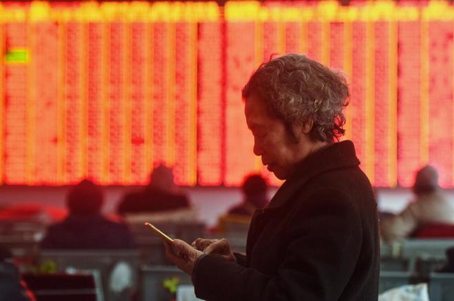 Una mujer consulta su teléfono ante un panel con los datos de la bolsa de Shanghai.