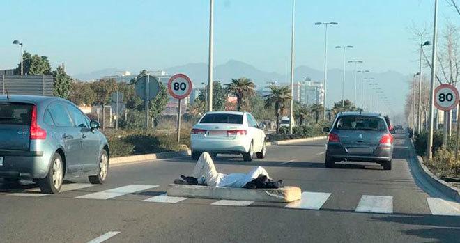 El hombre, acostado sobre un colchón en medio del paso de peatones, este lunes.