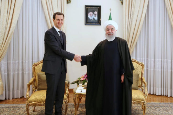 El presidente sirio, Bashar Asad, y el presidente iraní, Hasan Rohani, se saludan en la reunión de hoy.