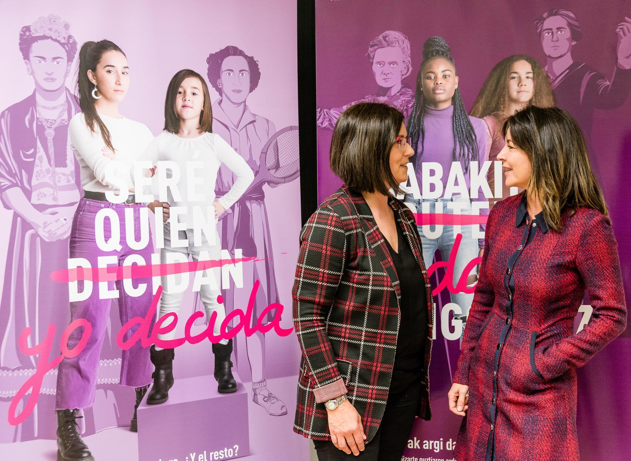 Izaskun Landada y Zuriñe Elordi ante el cartel de la campaña del 8-M.
