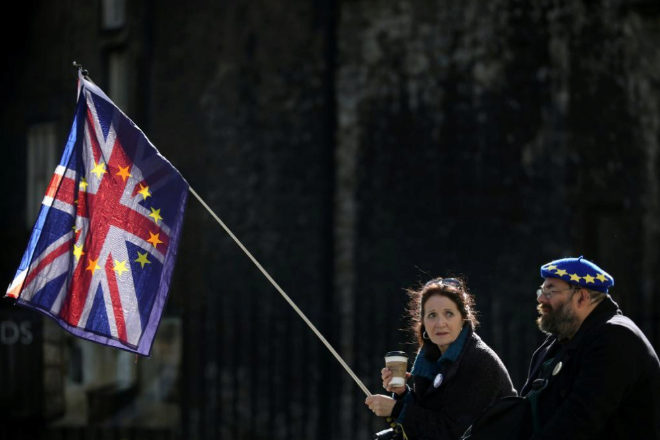 Dos activistas anti Brexit se sientan frente al Parlamento británico, en Londres.
