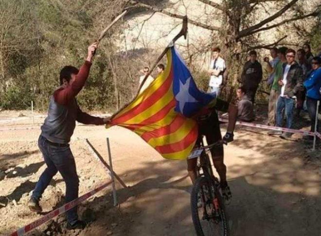 Un independentista coloca la estelada delante de Carlos Coloma.