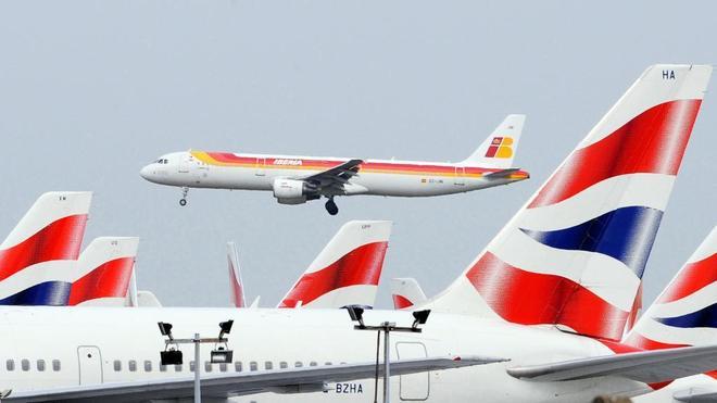 Un avión de pasajeros Airbus 321 de Iberia Airlines pasa sobre un avión de British Airways cuando aterriza en el aeropuerto de Heathrow, en el oeste de Londres
