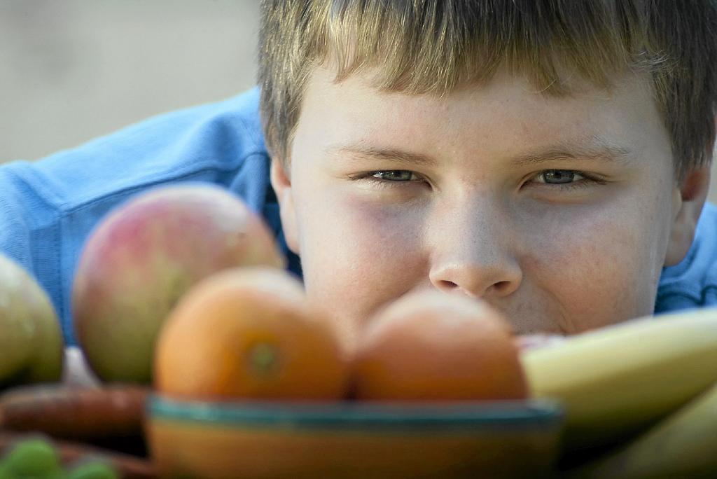 Un niño con sobrepeso observa unas frutas.