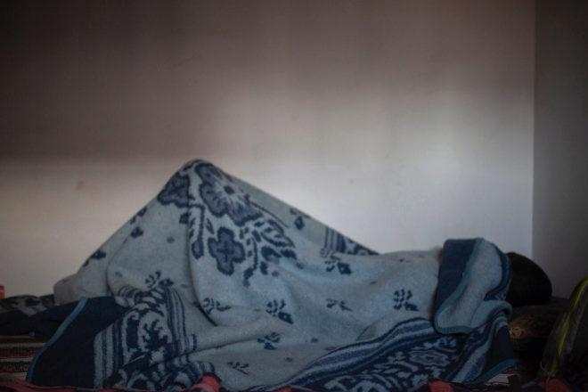 Una mujer migrante se refugia bajo una manta en Kenitra.