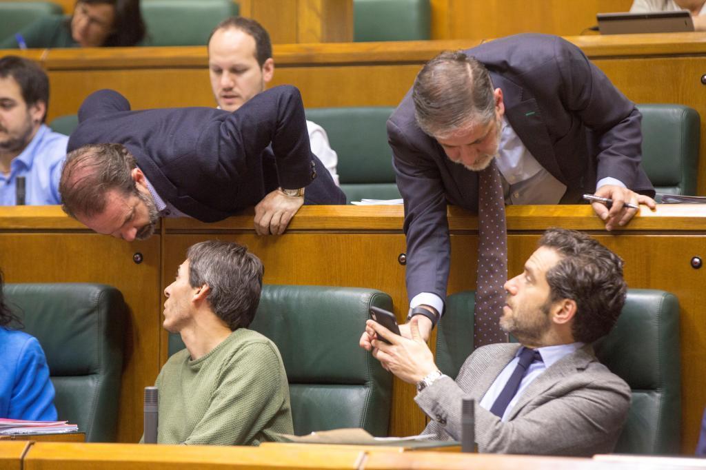 Parlamentarios de Elkarrekin Podemos y PP conversan en el pleno del Parlamento.