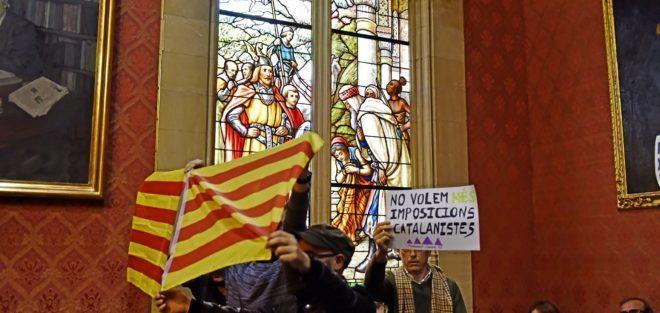 El independentista Amadeu Corbera tapa un cartel de la Fundació Jaume III con la bandera catalana, ayer, en el pleno del Consell.