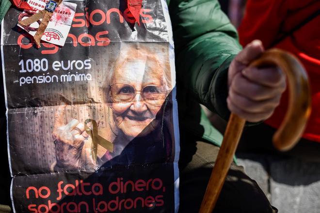 Un manifestante porta un cartel exigiendo una pensión de 1.080 en una manifestación celebrada en Bilbao.