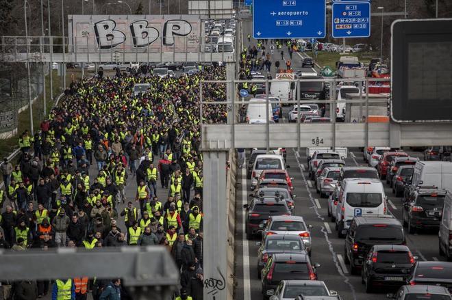 Miles de taxistas andando por la carretera que da acceso al aeropuerto de Barajas.