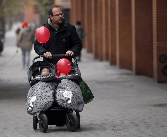 Un padre empuja un carrito con dos bebés en Madrid.