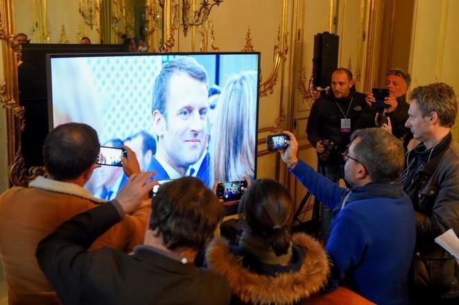 Varios periodistas hace fotos a una pantalla en la que aparece Emmanuel Macron, durante una sesión del Gran Debate Nacional en Burdeos (Francia).