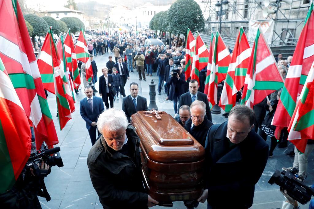 Allegados trasladan el féretro con los restos de Arzalluz hacia el interior de la parroquia de Azkoitia.
