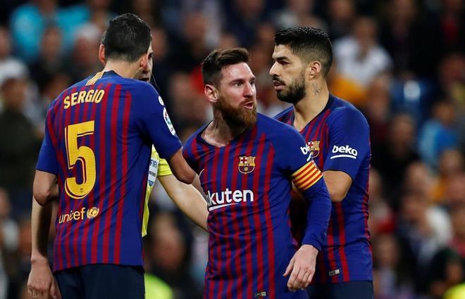 Messi, entre Busquets y Luis Suárez, busca con la mirada a Sergio Ramos.
