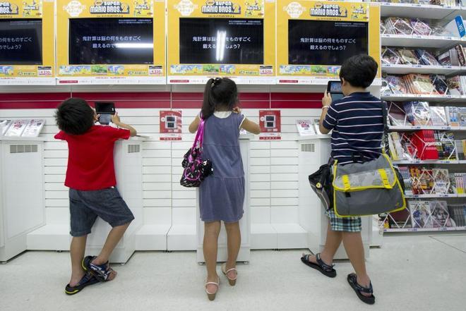 Tres niños juegan a la consola en Japón.