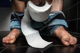 Un hombre sujeta un rollo de papel higiénico sentado en el váter.