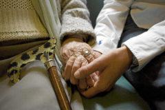 Una voluntaria coge la mano de la persona mayor a la que acompaña para paliar sus momentos de soledad.