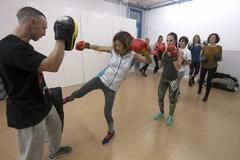Participantes del curso de defensa personal femenino se ejercitan con un entrenador.
