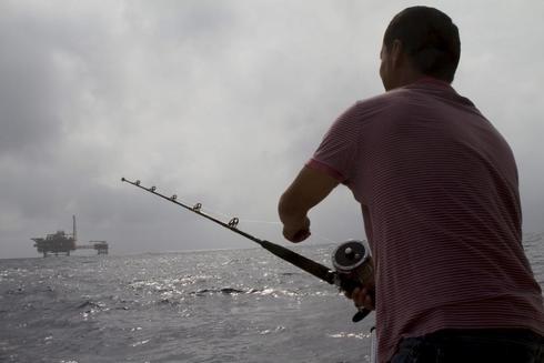 Un pescador faena frente al almacén de gas de Castor