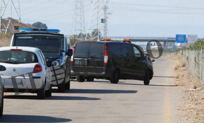 El furgón fúnebre y la policía abandonando el lugar donde apareció el cadáver.