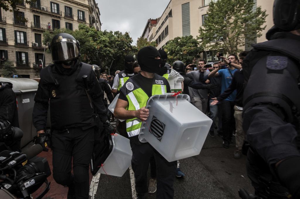 Imagen de Policía frente a un colegio en Barcelona requisando urnas