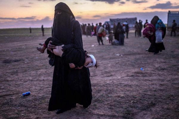 Una mujer sostiene a su hijo herido en su huida de Baguz.