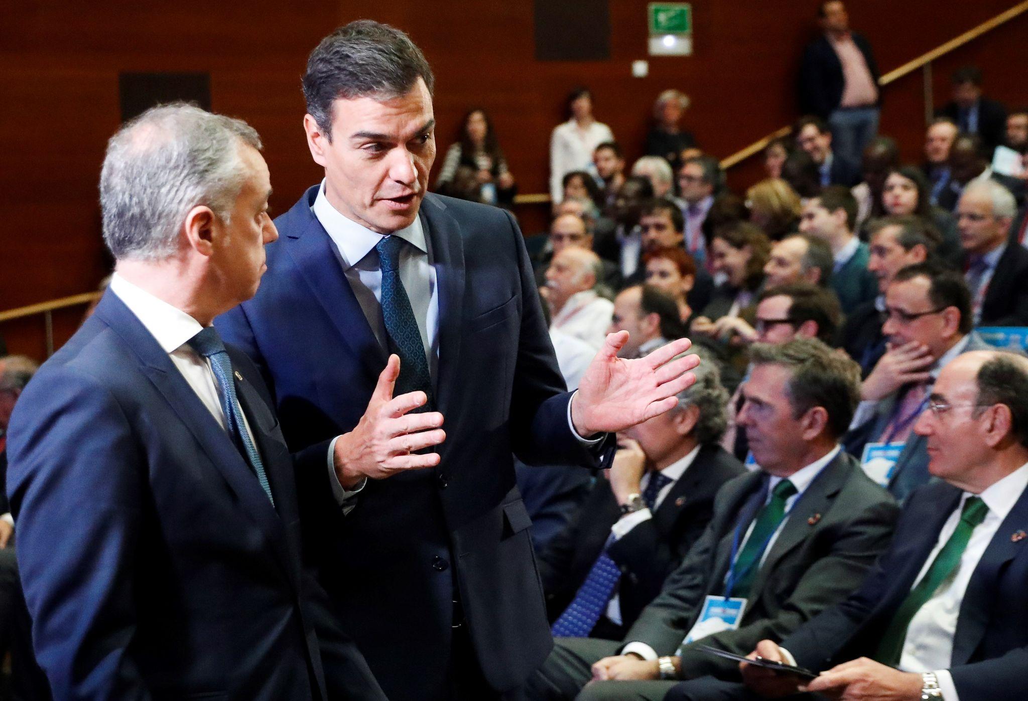 Urkullu y Sánchez conversan con Galán sentado entre el público.