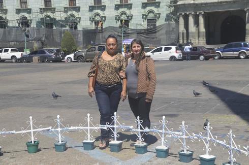 Vianey Clareth Hernández (izda.), madre de Hashly Angely Rodríguez, y Elida Esmeralda Salguero, madre de Keyla Rebeca López, dos de las 41 niñas fallecidas en un hogar en 2017, junto al altar con sus cruces en Ciudad de Guatemala. CRÉDITO: <HIT>Asier</HIT> Vera