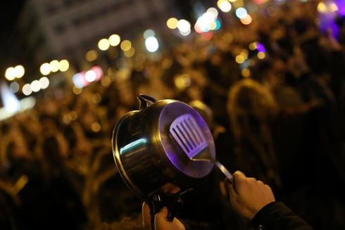 Women bang pots and pans during a protest at the start of a nationwide...