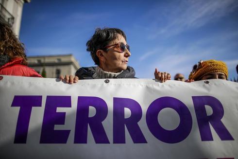 Una mujer, con una pancarta contra la violencia machista