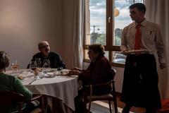 Un camarero atiende a un grupo de comensales invidentes.