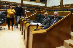En primer término el lehendakari y al fondo la parlamentaria del PP, Nerea Llanos, esperan a que se proceda a la suspensión de la sesión en una Cámara semivacía.