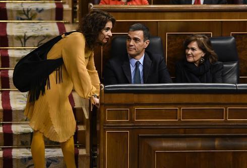 La ministra de Hacienda, María Jesús Montero, conversa con Pedro Sánchez y Carmen Calvo en un Pleno del Congreso.