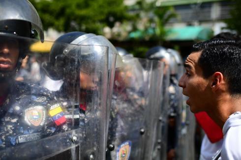 Un opositor trata de hablar con la policía bolivariana en Caracas.