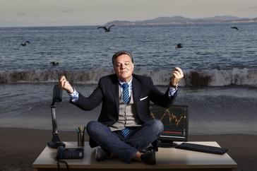 Un directivo con su mesa de trabajo en plena playa.