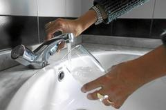 Una persona llena un vaso de agua del grifo.
