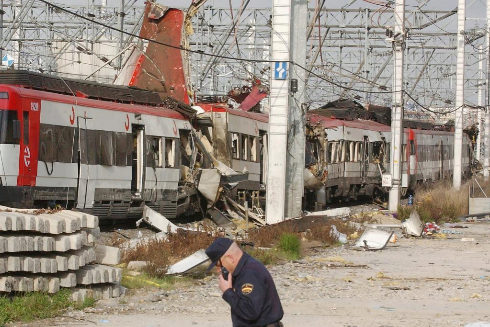 Un policía, junto a uno de los trenes dañados en los atentados del 11-M.