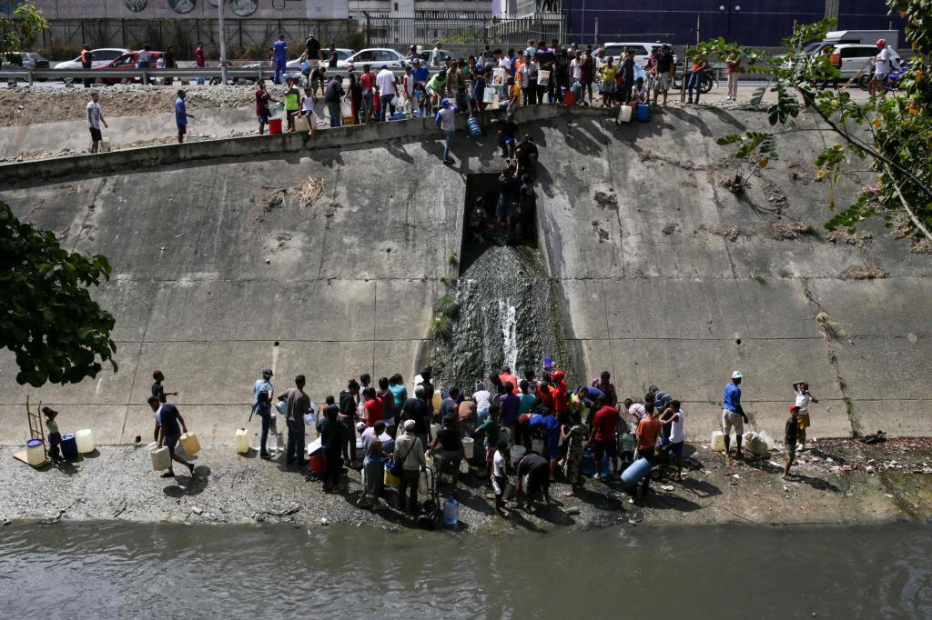 Personas intentando recoger agua en el insalubre río Guaire.