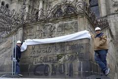 Unos operarios se disponen a cubrir una de las pintadas en la Catedral.