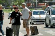 Turistas a su llegada al aeropuerto de Son Sant Joan con taxistas detrás. C. FORTEZA