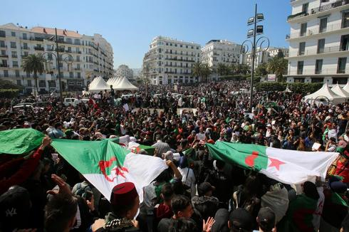 People take part in a protest demanding immediate political change in Algiers